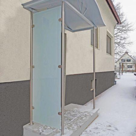 Geschwungenes Vordach aus Aluminium mit Seitenverglasung
